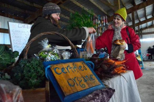 JUSTIN BURNETT PHOTOAnnie Jesperson of Deep Harvest Farm in Greenbank sells produce to Coupeville resident Ingrid Sechrist at the last day of 3 Sisters Cattle Company's fall farmers market.